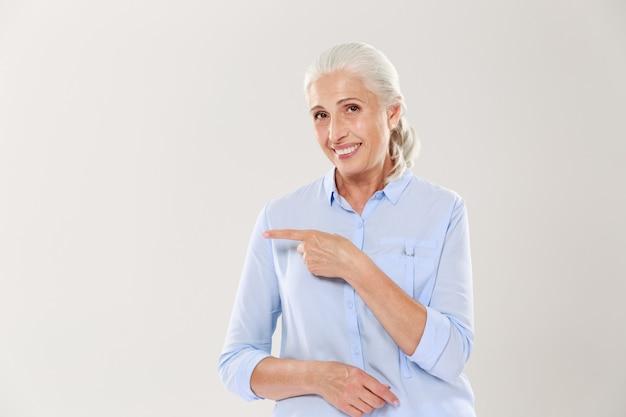 Веселая старушка в синей рубашке, указывая пальцем на пустой copyspace Бесплатные Фотографии