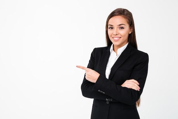 Copyspaceを指している幸せなビジネスの女性。 無料写真