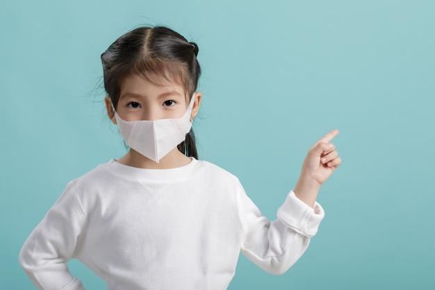 Маска респиратора азиатской девушки маленького ребенка нося для того чтобы защитить вспышку коронавируса и указывать рука к пустому copyspace Premium Фотографии
