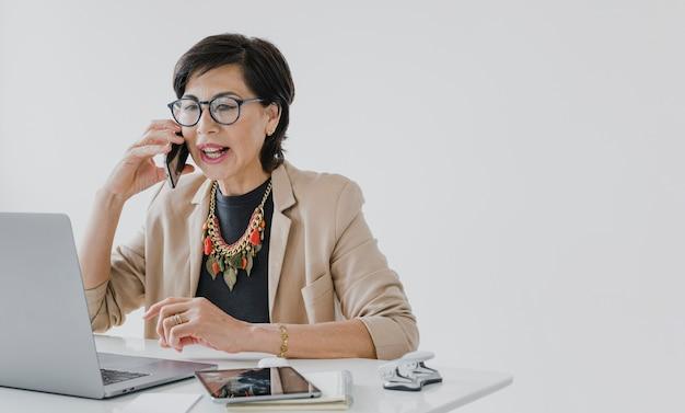 Copyspaceと電話で話しているネックレスを持つシニア 無料写真