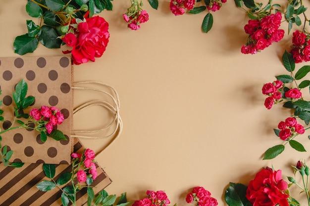 ハンドルの水玉とストライプとクラフトの背景に自然な赤いバラの包装袋。 copyspace付きフラットレイアウト Premium写真
