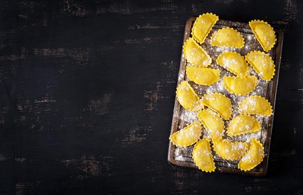 テーブルの上の未調理のラビオリ。イタリア料理。 copyspaceとトップビューの背景 Premium写真