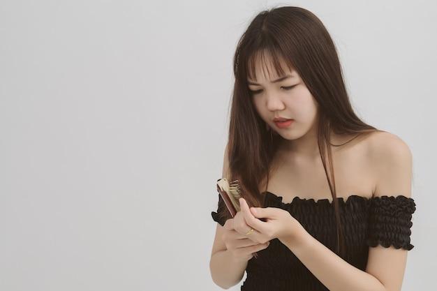 白の櫛と問題の髪を持つアジアの女性の長い髪の肖像画。この抜け毛のイメージ。 copyspace。 Premium写真