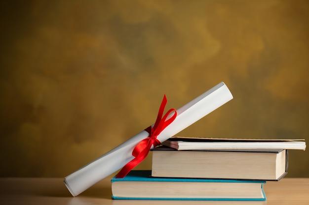証明書、書籍、copyspaceの木製テーブルの上のペンのスクロール Premium写真