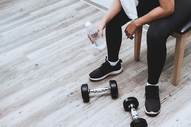 Фитнес девушка перерыв для питьевой воды, сидя с гантелями силовые тренировки с copyspace Premium Фотографии