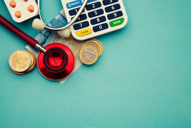 コイン、青の上の丸薬の山に赤い聴診器。 copyspace。薬と健康管理。 Premium写真