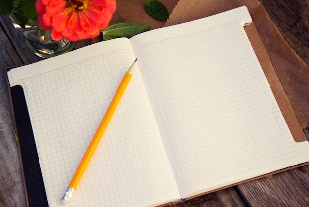 テキストの準備ができて。ピンクの花と古い木製のテーブルでノートブックを開きます。上面図。 copyspace。 Premium写真