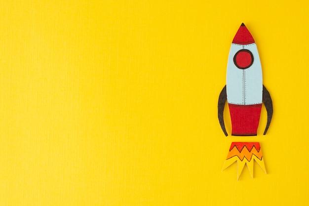 事業を開始します。収入、給料を増やしたり増やしたりする。カラフルな黄色に描かれたロケット。 copyspace。 Premium写真