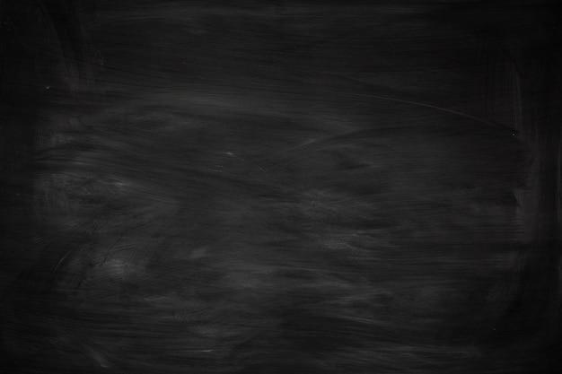 Copyspaceと黒グランジ汚れた質感。黒板や黒板の背景に抽象的なチョークがこぼれた。空のテンプレートとチョークの跡やあなたのすべてのデザインのためのマッサージの概念の壁紙。 Premium写真