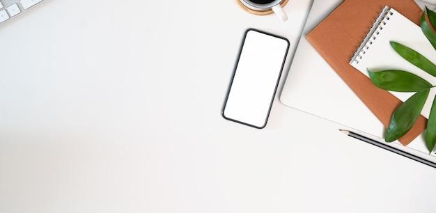 事務用品、空白の画面携帯電話、copyspaceと白いワークスペース Premium写真