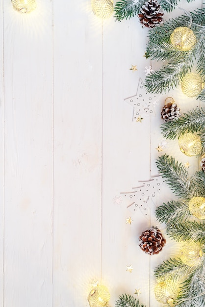 Рождественские светлые шарики с еловой веткой и конусом на белом деревянном, вид сверху copyspace Premium Фотографии