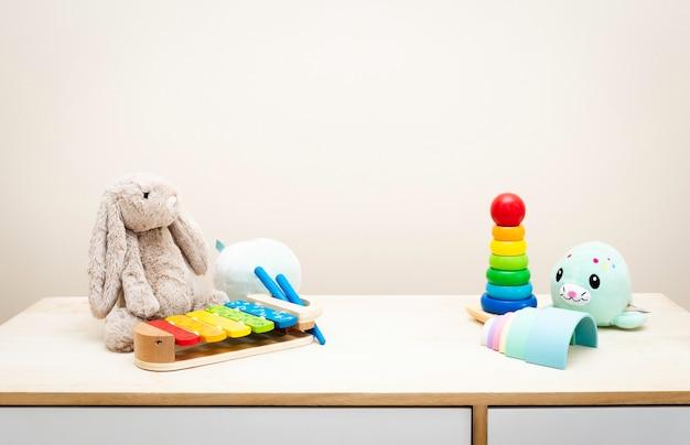 Copyspaceと木製のテーブルの壁のおもちゃのカラフルな子供のおもちゃの Premium写真