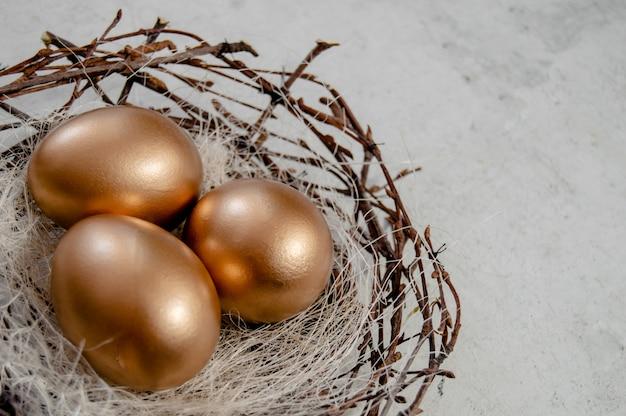 鳥の黄金のイースターエッグ素朴な背景の上に巣。イースター休暇の概念抽象的な背景copyspaceトップビューいくつかのオブジェクト。クローズアップ表示 Premium写真