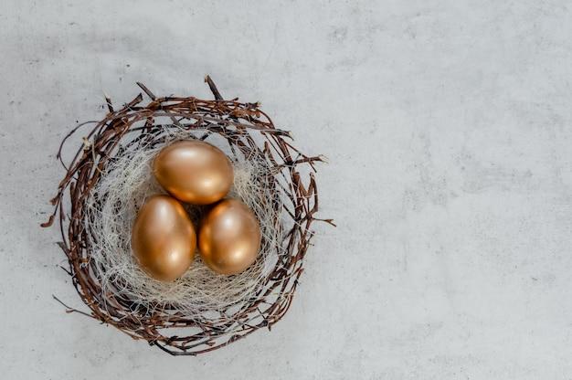 Золотые пасхальные яйца в гнезде птиц на деревенском фоне. взгляд сверху copyspace предпосылки конспекта концепции праздника пасхи несколько объектов. Premium Фотографии