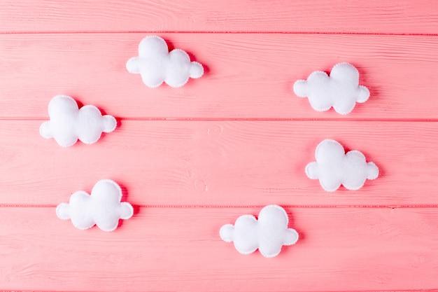 フレーム、ピンクの木製の背景にcopyspaceと白い雲を作ります。手作りのフェルトおもちゃ。 Premium写真