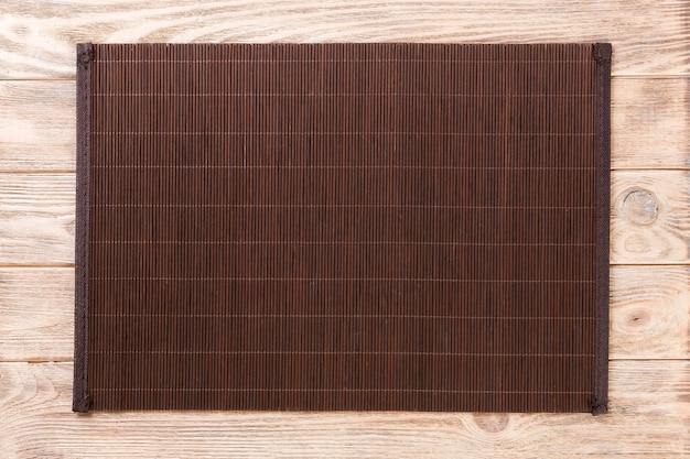 Пустая азиатская еда. темно-бамбуковая циновка на коричневом деревянном фоне сверху с плоской планировкой copyspace Premium Фотографии