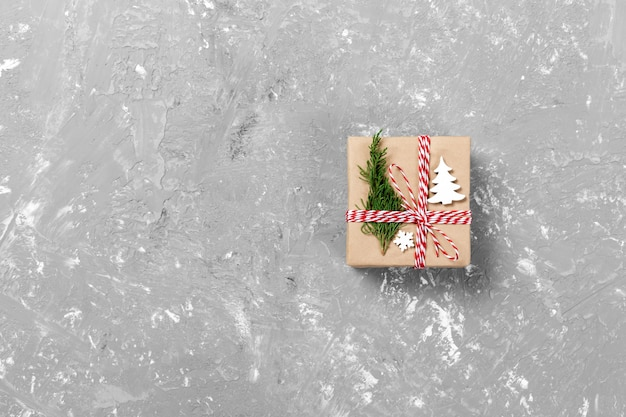 Подарочная коробка, завернутая в переработанную бумагу, с бантиком из ленты, с рождественским декором. цементный стол фон, copyspace Premium Фотографии