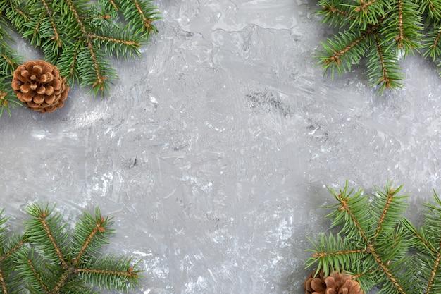モミの木フレームとコーンcopyspaceとクリスマスグレーセメント木製の背景。トップビューの空きスペース Premium写真