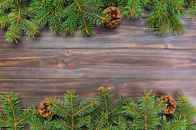 Предпосылка рождества серая деревянная с рамкой ели и copyspace конусов. вид сверху пустое место Premium Фотографии