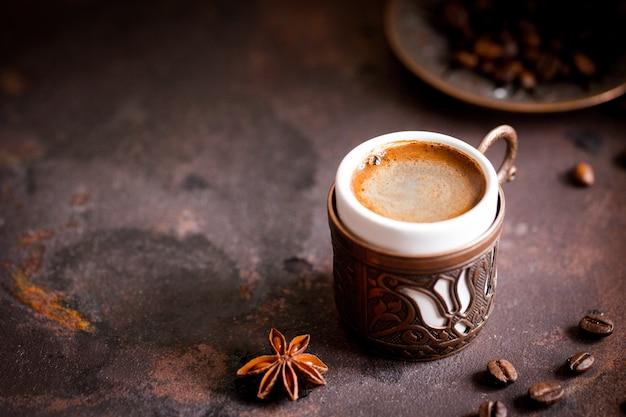 コーヒーカップと古いキッチンテーブルの豆。 copyspaceでトルココーヒーとトルコの喜び Premium写真
