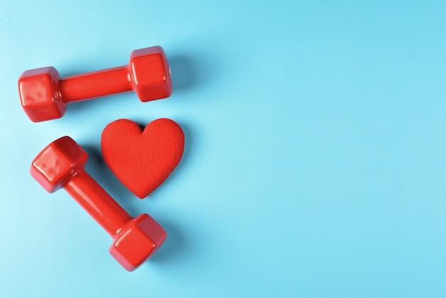 Предпосылка концепции спорта и фитнеса с copyspace с красным сердцем и гантелями на земле голубой черноты. вид сверху Premium Фотографии