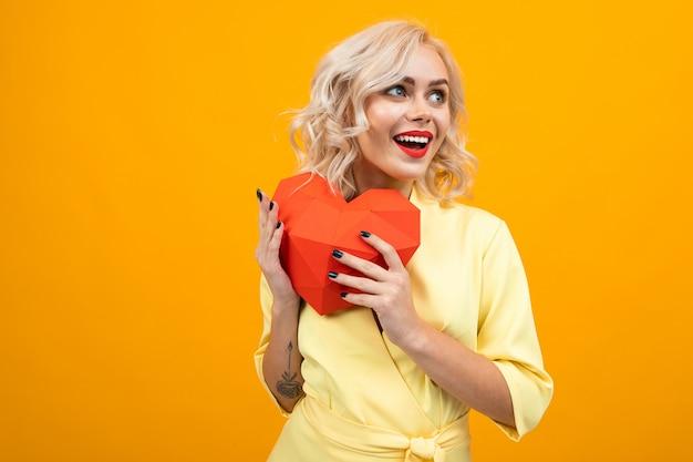 День святого валентина . портрет счастливой блондинки с макияжем с красной помадой с красным сердцем из бумаги на желтом с copyspace Premium Фотографии