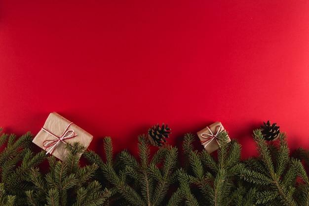 クリスマスツリーの枝、ギフト、赤、クリスマス、グリーティングカードcopyspaceの松ぼっくり。 Premium写真
