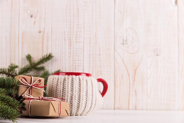 クリスマスツリーの枝、ギフト、マグカップ、クリスマス、グリーティングカードのホットドリンク。 copyspace。 Premium写真