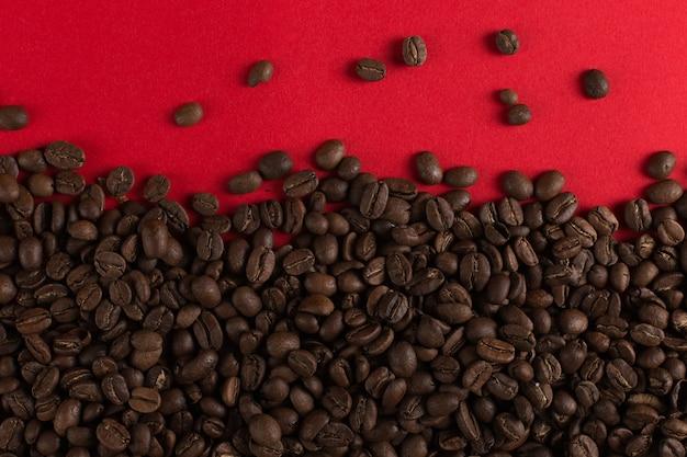 Кофейные зерна разбросаны на красной бумаге крупным планом, коммерческие copyspace. Premium Фотографии