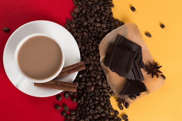 Кофейные зерна разбросаны по красной и желтой бумаге и белой чашке, корице, звездчатому анису, шоколаду, коммерческому copyspace. Premium Фотографии