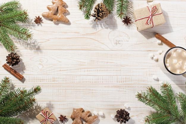 Горячий рождественский напиток с маршмеллоу в кружку железа и пряники, на белом столе. , праздник, открытка copyspace. Premium Фотографии