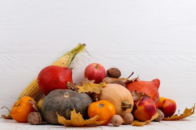さまざまな野菜、カボチャ、リンゴ、梨、ナッツ、トウモロコシ、トマト、白い木製の背景に乾燥した葉。秋の収穫、copyspace。 Premium写真
