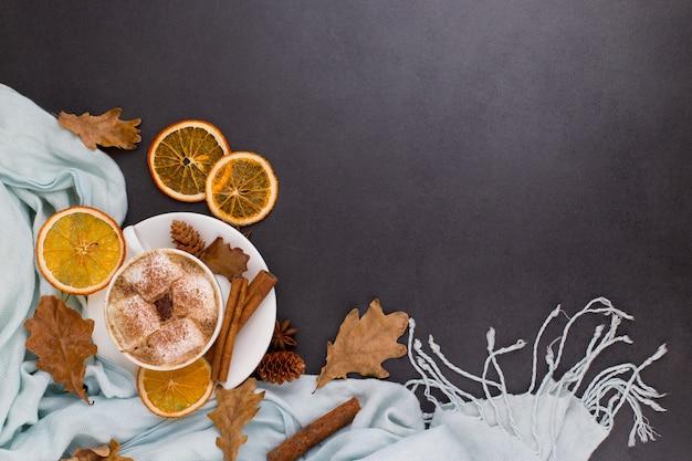 Чашка кофе с маршмеллоу, какао, шарф, листья, сушеные апельсины, специи, на сером фоне. вкусный горячий осенний напиток, утреннее настроение. copyspace. Premium Фотографии