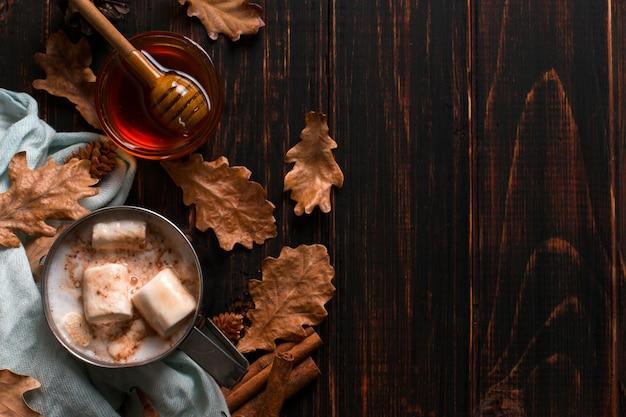 Железная кружка с какао, медом, зефиром, специями, на фоне шарфа, сухими листьями на деревянном столе. осеннее настроение, согревающий напиток. copyspace. Premium Фотографии