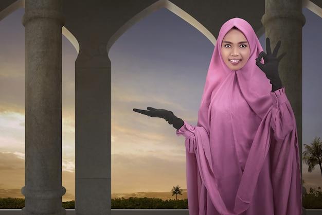 Copyspaceのための空の領域を示す若いアジア女性イスラム教徒 Premium写真