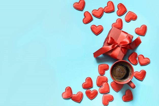 День святого валентина. подарок с красной лентой, чашка кофе и сердца на синем. вид сверху. copyspace. Premium Фотографии