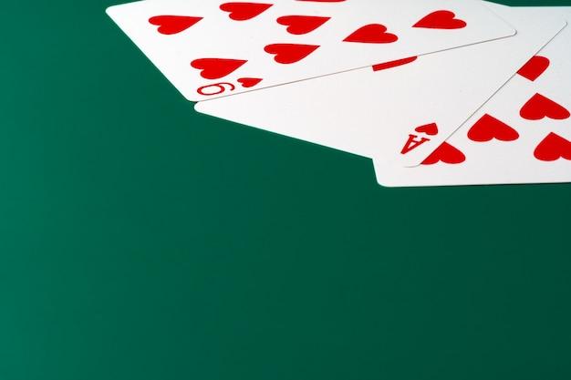 Игральные карты на зеленом столе крупным планом, copyspace Premium Фотографии