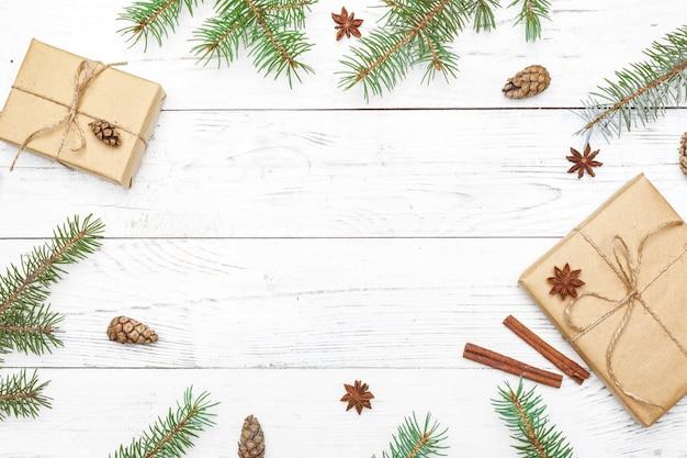 Подарки на новый год, завернутые в крафт-бумагу возле еловых веток и шишек на белом фоне деревянных вид сверху copyspace Premium Фотографии