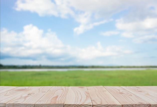 空の木の板テーブルの上にぼやけている青い空と川の背景。ディスプレイ用copyspaceまたは製品のモンタージュ Premium写真