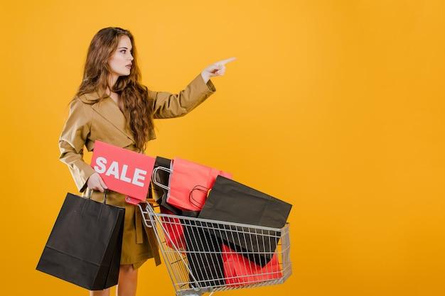 販売サインと黄色で分離されたカートでカラフルなショッピングバッグでcopyspaceを指しているトレンチコートの若い女性 Premium写真