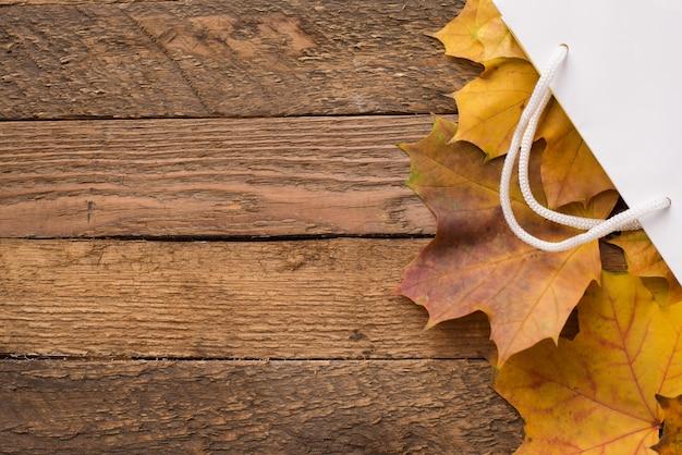 Белый пакет с осени высушил желтый цвет выходит на деревянное, copyspace. осенняя распродажа Premium Фотографии