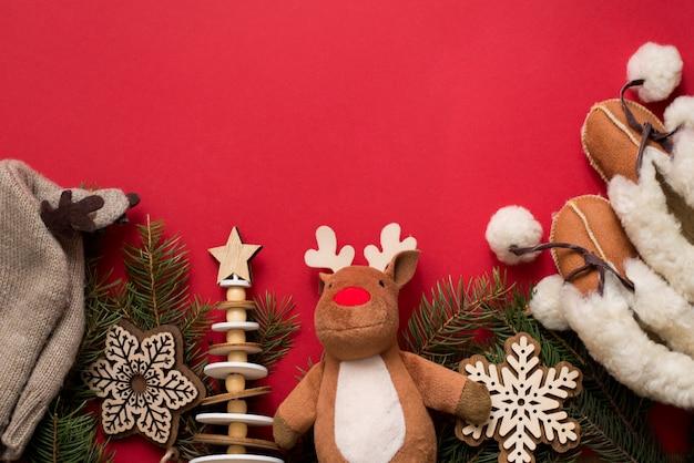 赤ちゃんのアクセサリーの帽子とブーツ、木のおもちゃ、赤、copyspaceのクリスマスのモミの木。子供の頃の休日の概念 Premium写真
