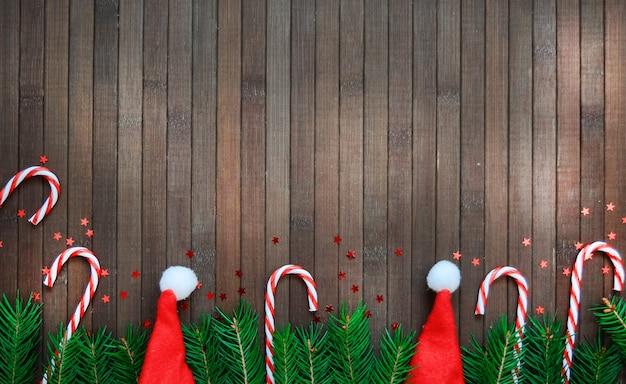 木の枝、サンタ帽子、キャンディー星、松ぼっくり、木製の新年の休日パターンのクリスマス組成。 copyspace。 Premium写真