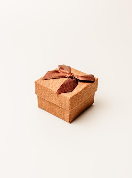 Винтажная подарочная коробка с коричневой лентой на белой предпосылке, изолятом. copyspace. Premium Фотографии