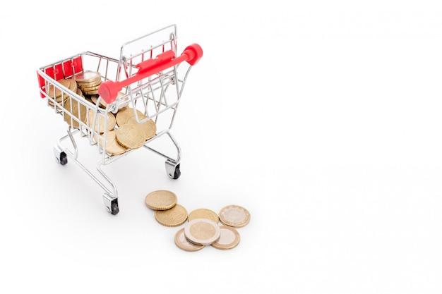 白い背景の上からそれから落ちてくるユーロ硬貨のショッピングカート。失敗、貧困、破産の概念図。スーパーマーケットのショッピング、セール、キャッシュバックのテーマ。テキストのcopyspace。 Premium写真