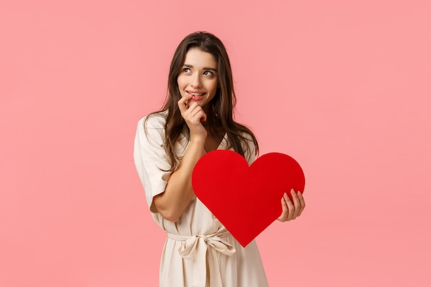 Coquettish and silly, dreamy cute, alluring brunette woman in dress, look left imaging perfect date, touching lip and smiling with tempting, eager expression, holding valentines heart, love concept Premium Photo
