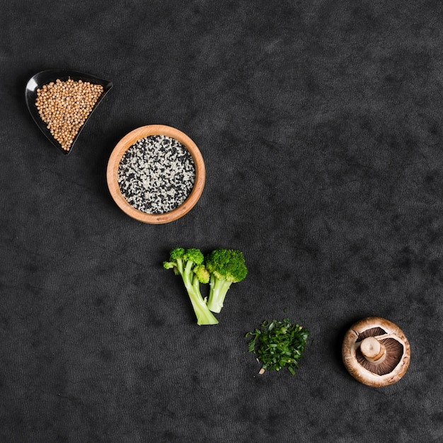 Coriander seeds; sesame seeds; broccoli; chopped chives and mushroom on black texture backdrop Free Photo