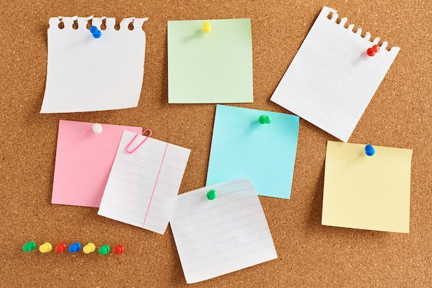 Cork board with a pinned colored blank notes Premium Photo
