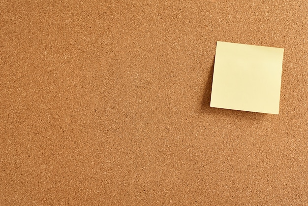 Cork board with a yellow paper blank note Premium Photo
