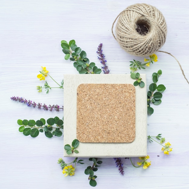 Cork frame with twig and flowers and string spool on wooden textured backdrop Free Photo